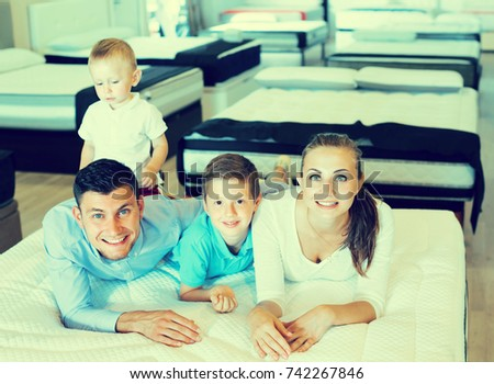 Cheerful family with kids are testing quality of mattress in store.