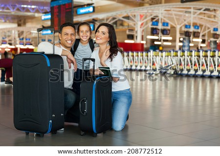 cheerful family with luggage bags at airport - stock photo