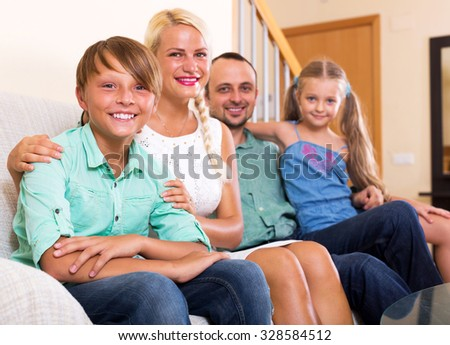 Cheerful family with two little kids on couch indoors. Focus on the boy - stock photo