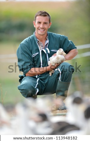 Cheerful farmer holding duck in his arms - stock photo