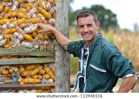 Cheerful farmer standing by corn silo - stock photo