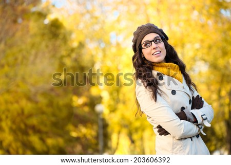 Cheerful fashion woman wearing glasses and warm clothes in autumn. Beautiful brunette with eyewear, raincoat, wool cap and scarf. - stock photo