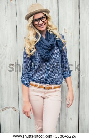 Cheerful fashionable blonde posing outdoors on wooden background - stock photo