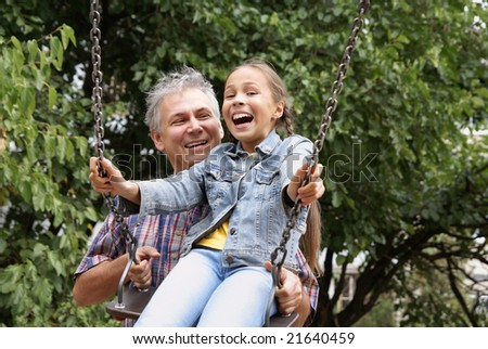 Cheerful father and daughter having fun on playground outdoors - stock photo