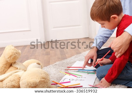 Cheerful father and son are playing at home. They are drawing pictures with varicolored pencils. The boy is sitting and looking at the image with interest. The man is embracing him - stock photo