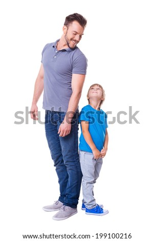 Cheerful father and son. Father and son standing back to back and looking at each other while standing isolated on white - stock photo