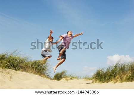 Cheerful father and son holding hands and jumping on sand at beach - stock photo