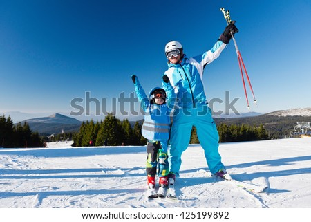 Cheerful father and son on ski slope - stock photo
