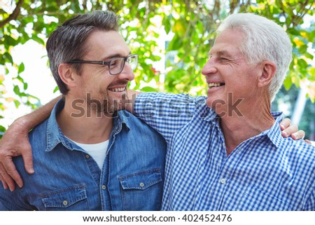 Cheerful father and son with arm around while standing outdoors - stock photo