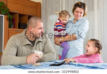 Cheerful father with banknotes sitting at table, happy family staying nearby. Focus on girl - stock photo