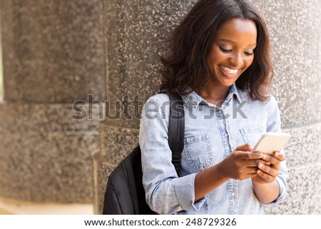 cheerful female afro american university student using cell phone - stock photo