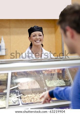 Cheerful female baker listening to a student in the queue of the cafeteria in the campus - stock photo