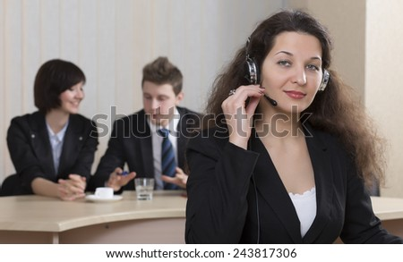 Cheerful female customer support officer. Portrait of smiling cheerful customer support phone operator in headset with her co-workers on the background - stock photo