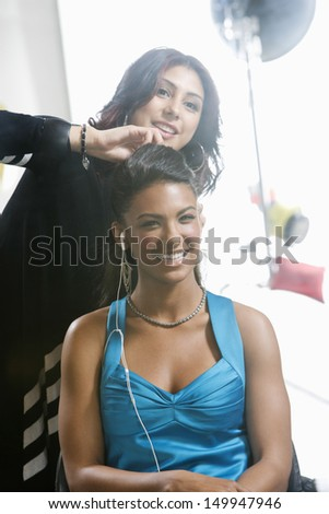 Cheerful female fashion model with smiling hairstylist - stock photo