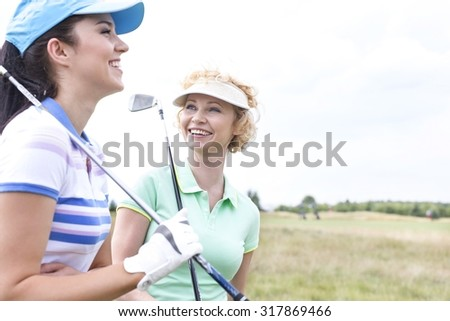 Cheerful female friends at golf course - stock photo