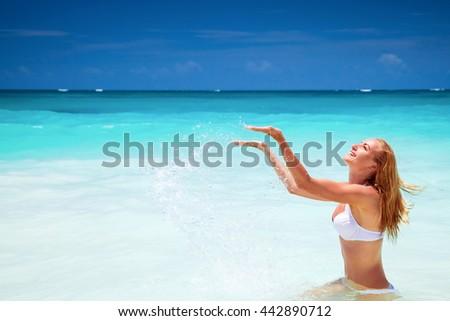 Cheerful female on the beach, splashing refreshing water, enjoying summer holidays on the beach resort, happy active lifestyle - stock photo