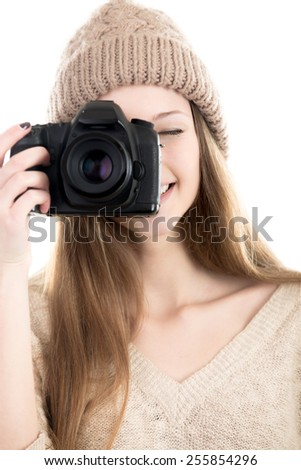Cheerful female photographer wearing casual style clothes, smiling, taking pictures with digital camera, teenage girl hobby photography - stock photo