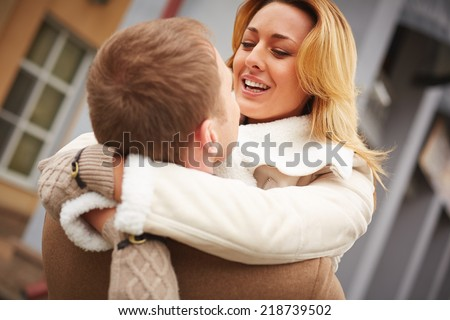 Cheerful female smiling on her boyfriend while embracing him - stock photo