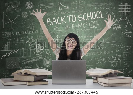 Cheerful female student expressing happiness in the classroom - stock photo