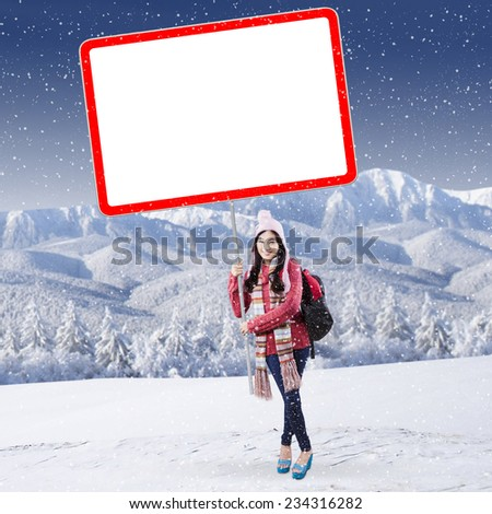 Cheerful female student in winter clothes holding blank board at snowy mountain - stock photo