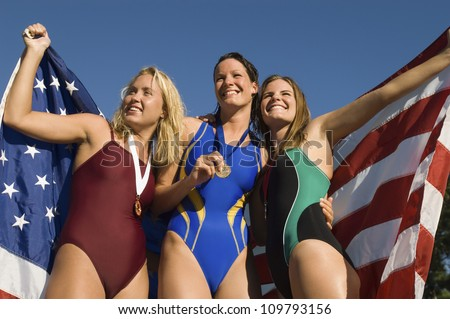 Cheerful female swimmers standing together holding a American flag - stock photo