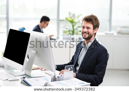 Cheerful financial manager working on computer