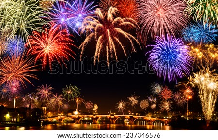 Cheerful fireworks display in the city, with lots of colorful bangs rising high into the night sky, with black copyspace - stock photo