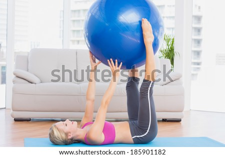Cheerful fit blonde holding exercise ball between legs at home in the living room - stock photo