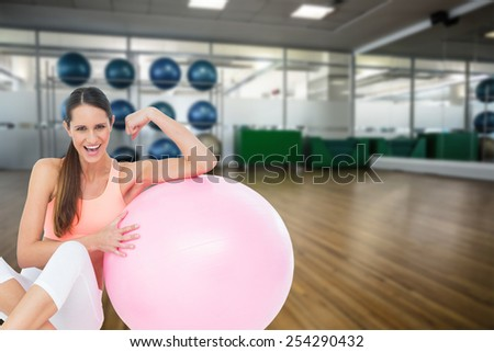 Cheerful fit woman flexing muscles by fitness ball against large empty fitness studio with shelf of exercise balls - stock photo