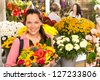 Cheerful florist woman showing colorful flowers market shop retail - stock photo