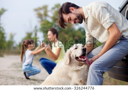 Cheerful friendly family is resting in park. The man is playing with dog and leaning on car. The mother and daughter are kneeling and holding hands. They are smiling - stock photo