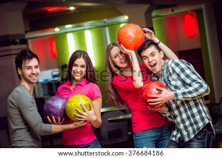 Cheerful friends at the bowling alley with the balls