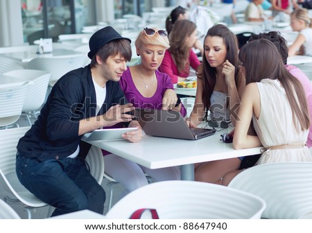 Cheerful friends browsing internet in a restaurant