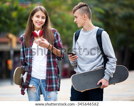 Cheerful friends carrying skateboards and walking through city - stock photo