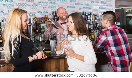 Cheerful friends drinking and chatting with barman at bar counter