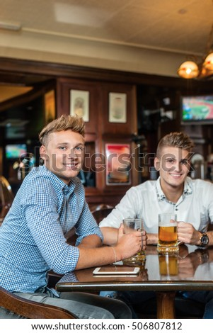 Cheerful friends drinking beer in pub