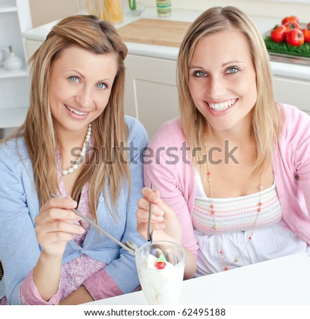 Cheerful friends eating an ice cream and smiling at the camera in the kitchen at home - stock photo