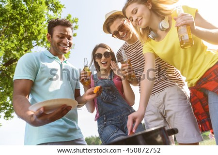 Cheerful friends eating barbecue in nature
