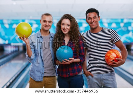 Cheerful friends holding balls while standing against bowling alleys