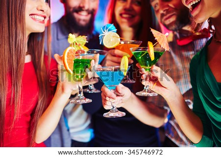 Cheerful friends holding martini glasses with cocktails