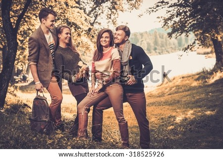 Cheerful friends in autumn park - stock photo
