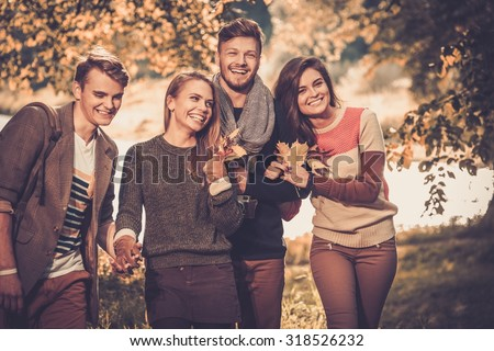 Cheerful friends in autumn park - stock photo