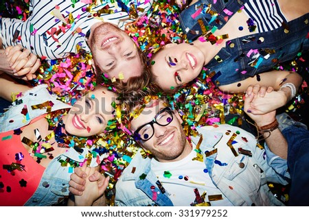 Cheerful friends lying on the floor covered with confetti in the night club - stock photo
