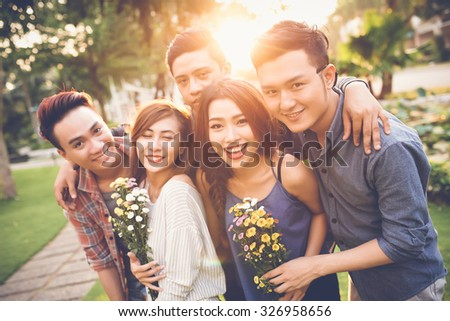Cheerful friends posing with flowers against sunset - stock photo