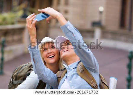 cheerful friends taking self portrait using cell phone at tourist's attraction - stock photo