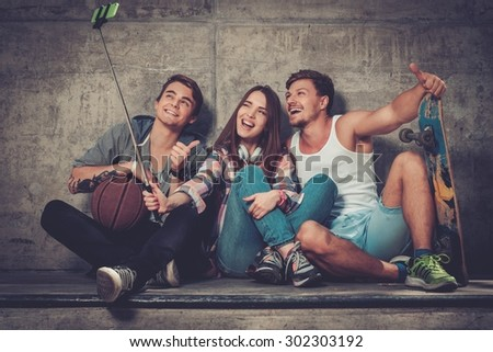 Cheerful friends with with skateboard taking selfie outdoors - stock photo