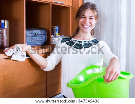 Cheerful girl cleaning shelves and tops in living room - stock photo
