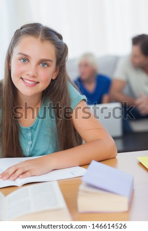 Cheerful girl doing her homework with her family behind her - stock photo