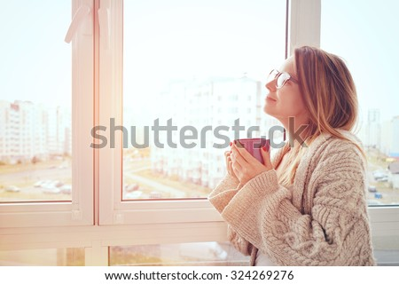 cheerful girl drinking coffee or tea in morning sunlight near window - stock photo