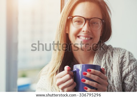 cheerful girl drinking coffee or tea in morning sunlight near window - stock photo